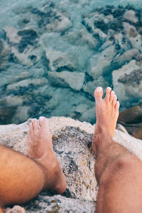 Les jeunes bravent l'homme s'asseyant sur une haute falaise au-dessus de l'océan images libres de droits