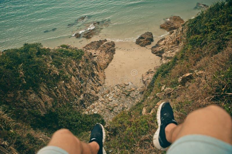 Les jeunes bravent l'homme s'asseyant sur une haute falaise en pierre au-dessus d'océan Vue supérieure photos libres de droits