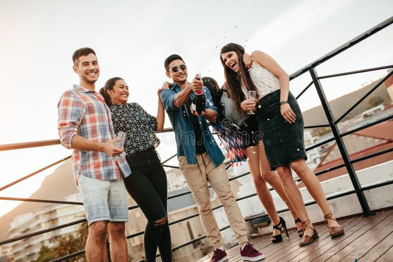 Les jeunes célébrant avec le champagne à la partie sur le dessus de toit photos libres de droits