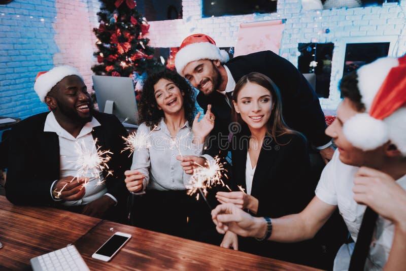 Les jeunes célébrant la nouvelle année dans le bureau moderne image libre de droits