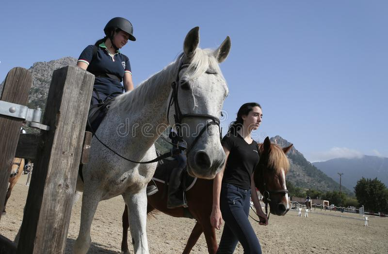 Les jeunes cavaliers et entraîneur avant une concurrence locale de cheval en Majorque marchent photo libre de droits