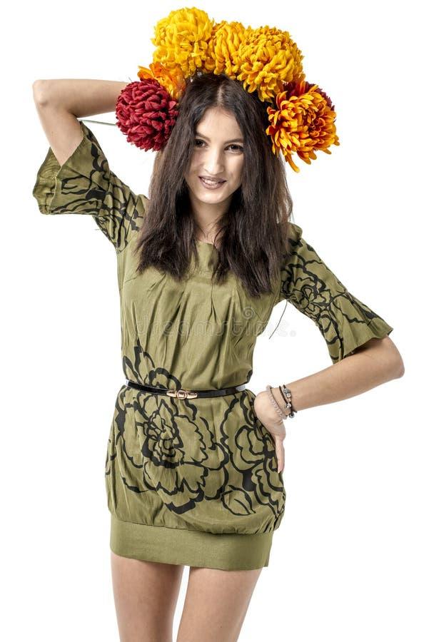 Les jeunes cheveux gais minces de brun de fille dansent avec un bouquet des fleurs colorées sur sa tête image stock