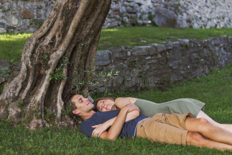 Les jeunes couplent dans l'amour se reposant sous un arbre dans un ch?teau photos libres de droits