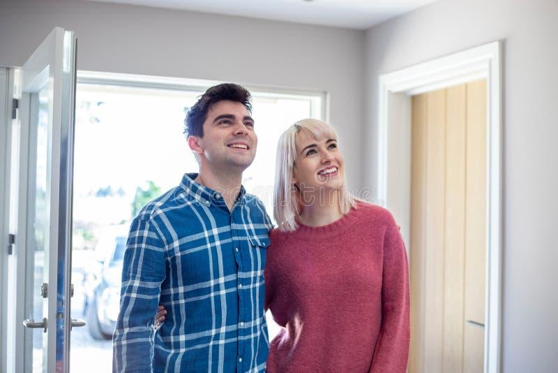 Les jeunes couplent le regard autour de la nouvelle maison à louer ou acheter ensemble images libres de droits