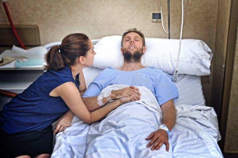 Les jeunes couples à la chambre d'hôpital équipent se situer dans la femme inquiétée par lit tenant ses soins de main image stock
