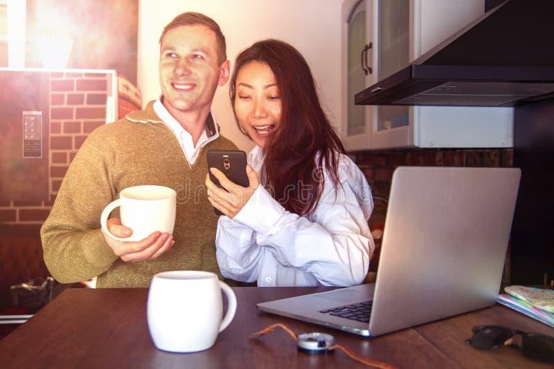Les jeunes couples à la maison près de l'ordinateur portable boivent le café et rire Couples internationaux heureux faire l'achat photographie stock libre de droits