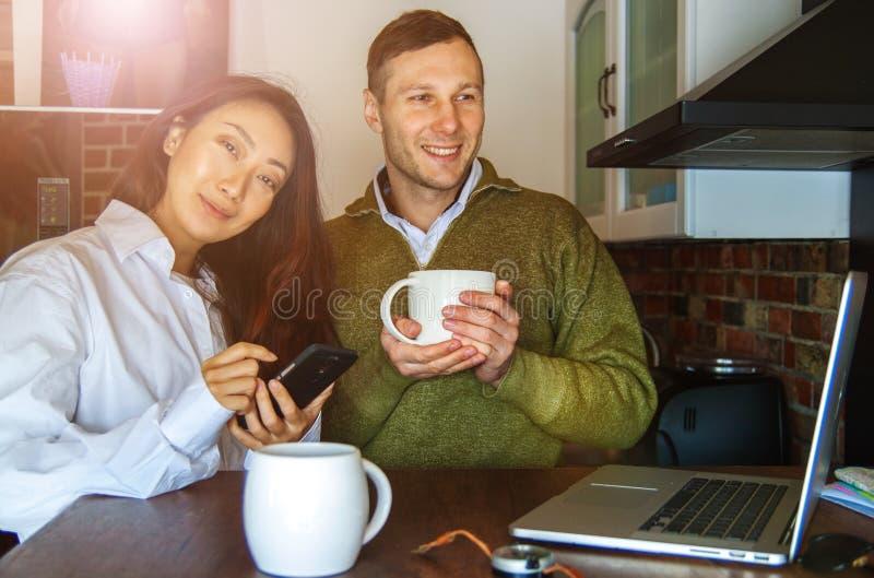 Les jeunes couples à la maison près de l'ordinateur portable boivent le café et rire Couples internationaux heureux faire l'achat photos libres de droits