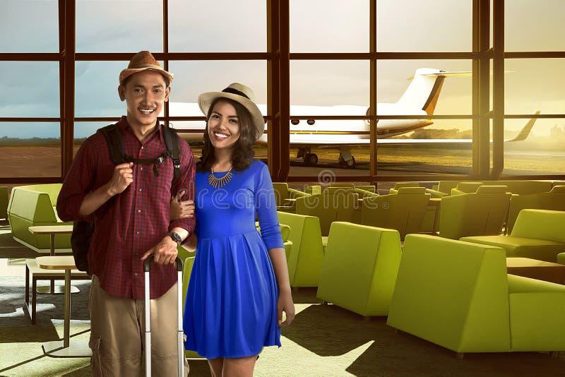 Les jeunes couples asiatiques dans l'aéroport sont heureux image libre de droits