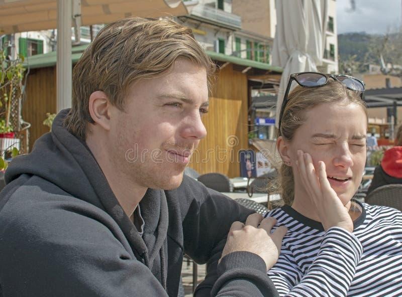 Les jeunes couples beaux se reposent dans le café et le strabisme en soleil rigide photos libres de droits