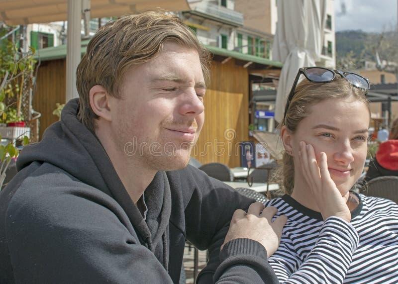 Les jeunes couples beaux se reposent dans le café et le strabisme en soleil rigide photo libre de droits