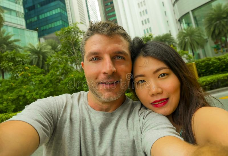 Les jeunes couples caucasiens asiatiques mélangés heureux et attrayants d'appartenance ethnique dans l'amour prenant le selfie dé image libre de droits