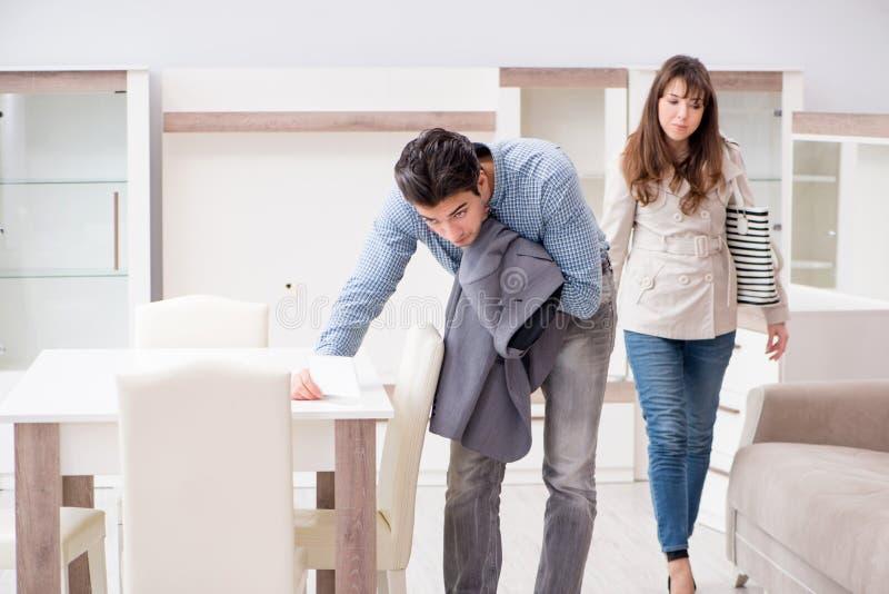 Les jeunes couples déçus par le prix dans le magasin de meubles photographie stock
