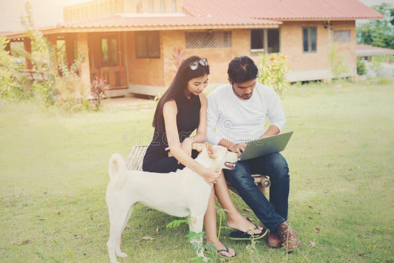 Les jeunes couples d'éducation se reposant sur le banc jouent avec le chien dans photo libre de droits
