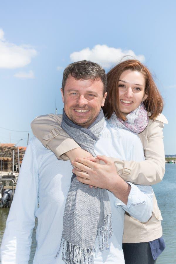 les jeunes couples dans l'amour étreignant près du côté de mer mettent en communication photo libre de droits