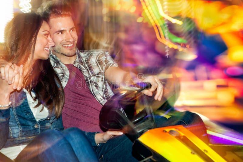 Les jeunes couples dans l'amour dans une voiture de butoir/dodgem montent photos stock