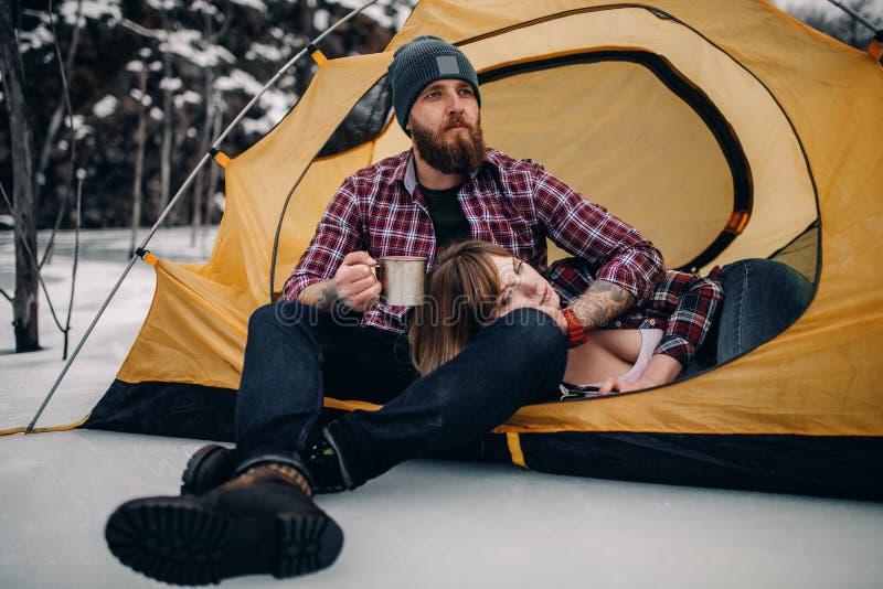 Les jeunes couples dans la tente de touristes pendant l'hiver augmentent Le type boit du thé chaud de la tasse en métal, mensonge image stock