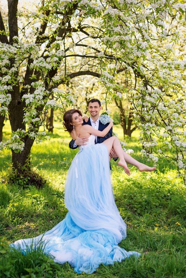 Les jeunes couples de mariage embrassant en ressort de floraison font du jardinage Amour et thème romantique images libres de droits