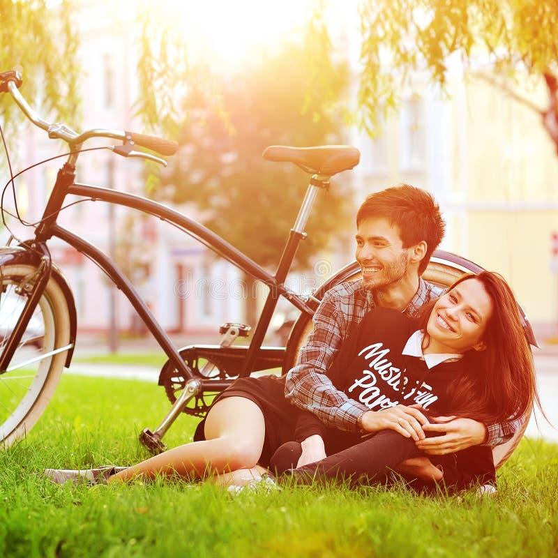Les jeunes couples de sourire heureux se situant en parc près d'un vintage font du vélo images libres de droits