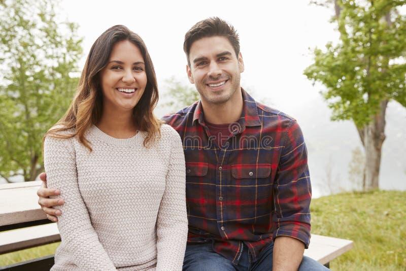 Les jeunes couples de sourire reposent l'embrassement en parc images libres de droits