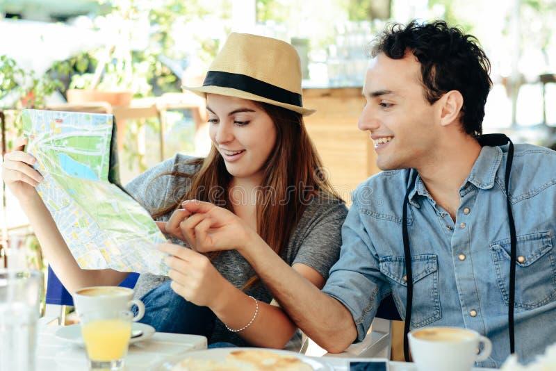 Les jeunes couples de touristes regardent une carte image libre de droits
