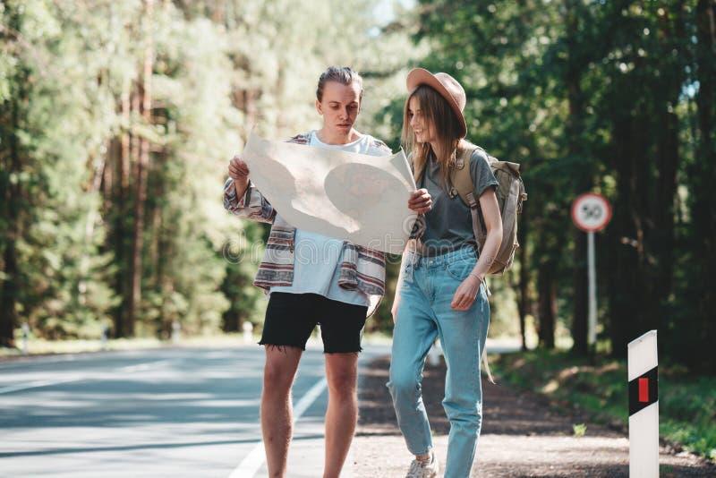 Les jeunes couples des hippies se tiennent prêt le côté de la route et du regard sur la carte de site photographie stock