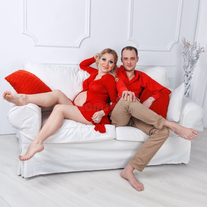 Les jeunes couples enceintes heureux se sont habillés dans l'étreinte rouge photos libres de droits