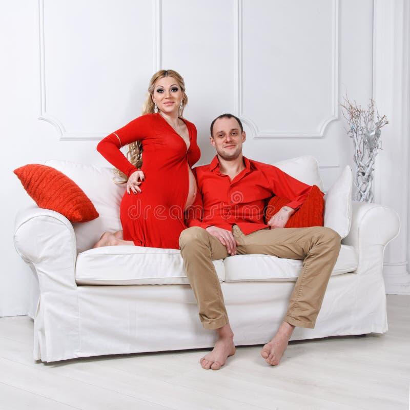 Les jeunes couples enceintes heureux se sont habillés dans l'étreinte rouge photos stock