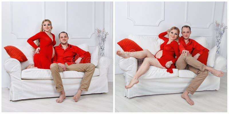 Les jeunes couples enceintes heureux se sont habillés dans l'étreinte rouge photo libre de droits