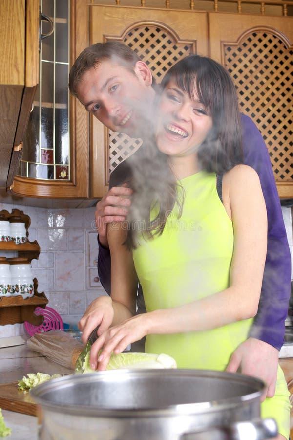 Les jeunes couples font cuire à la maison image stock