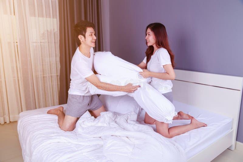 Les jeunes couples gais ayant un combat d'oreiller de traversin sur le lit dans soient image stock