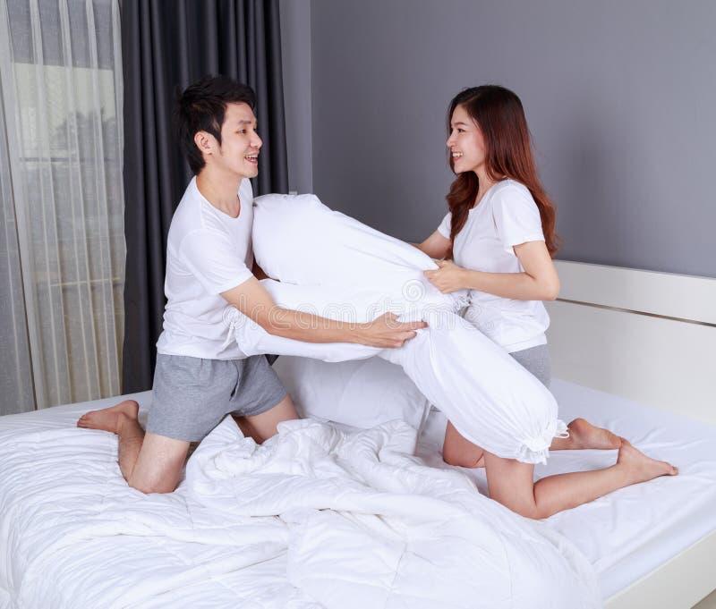 Les jeunes couples gais ayant un combat d'oreiller de traversin sur le lit dans soient photos stock