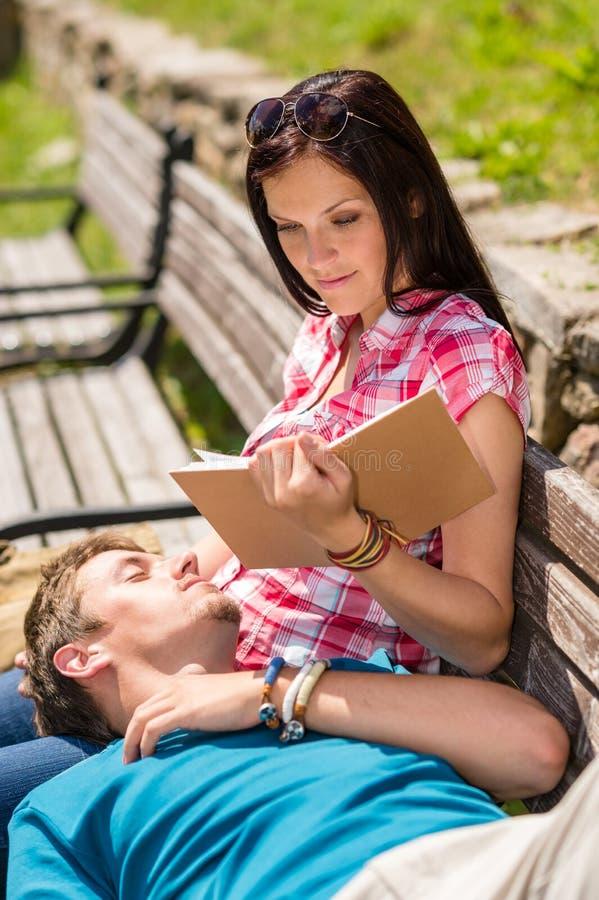 Les jeunes couples heureux détendent sur le stationnement de banc photographie stock libre de droits