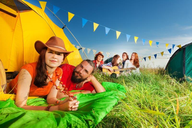Les jeunes couples heureux dans la tente appréciant le camp se déclenchent photographie stock