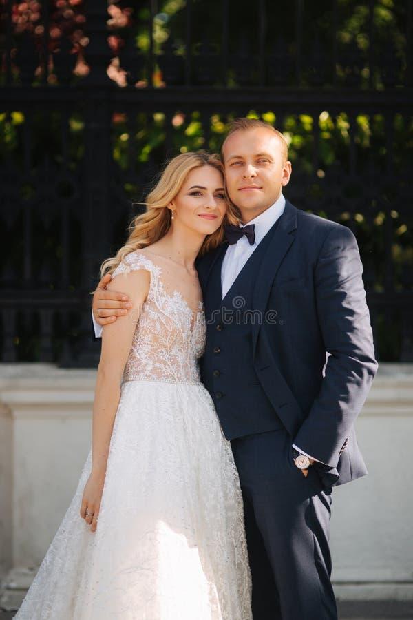 Les jeunes couples heureux dans leur jour du mariage passent le temps en parc Fond vert image libre de droits