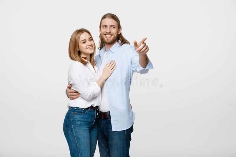 Les jeunes couples heureux de portrait aiment sourire embrassant le doigt de point pour vider l'espace de copie, l'homme et le so images stock