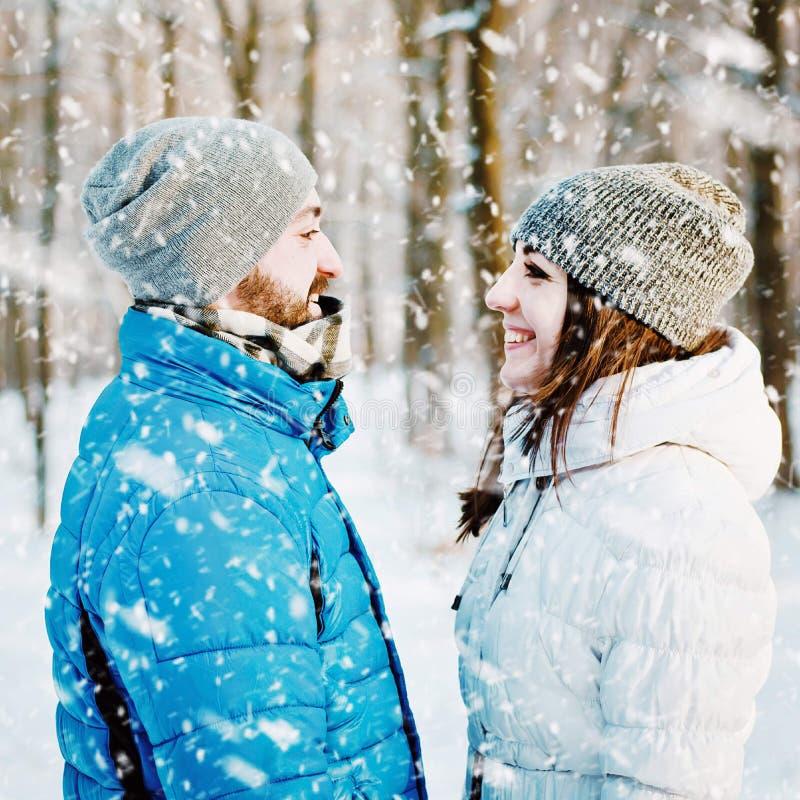 Les jeunes couples heureux en hiver stationnent avoir l'amusement images libres de droits