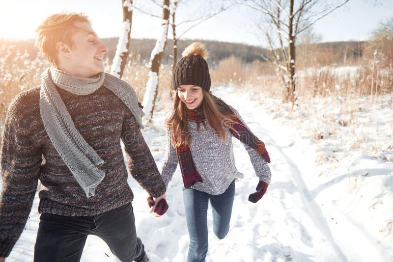Les jeunes couples heureux en hiver stationnent avoir l'amusement Famille à l'extérieur photo libre de droits