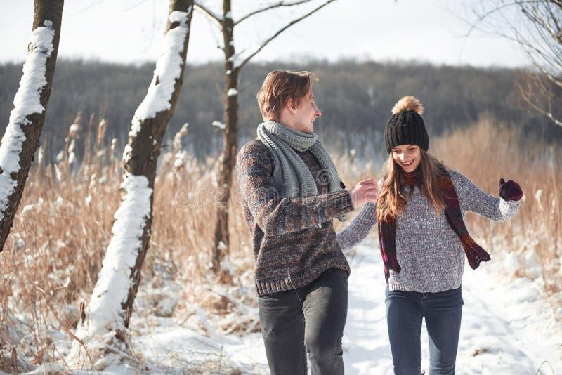 Les jeunes couples heureux en hiver stationnent avoir l'amusement Famille à l'extérieur image stock