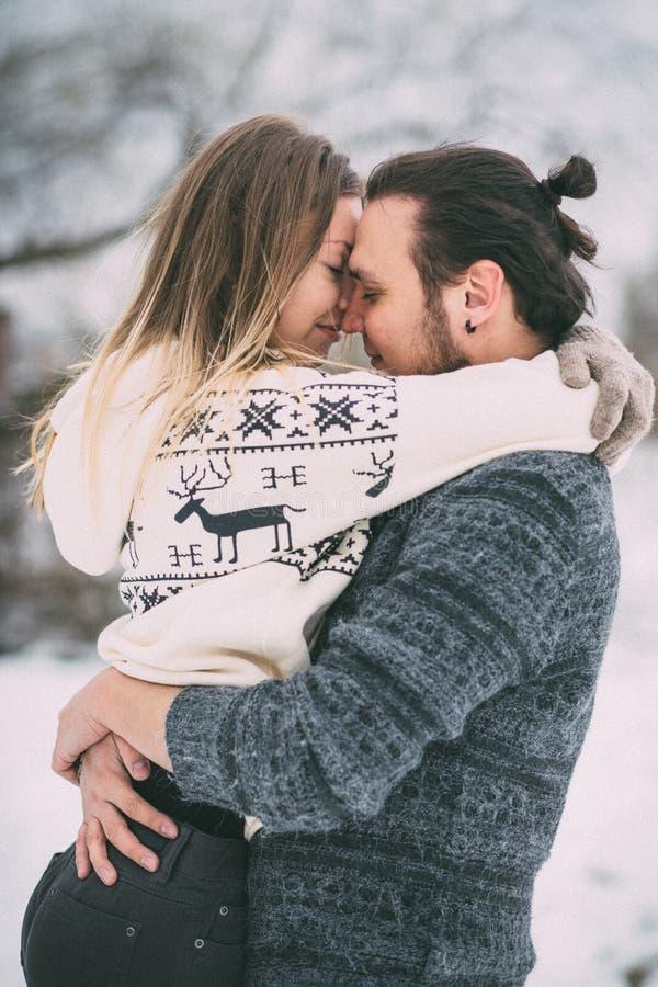 Les jeunes couples heureux en hiver stationnent avoir l'amusement Famille à l'extérieur Amour photos libres de droits