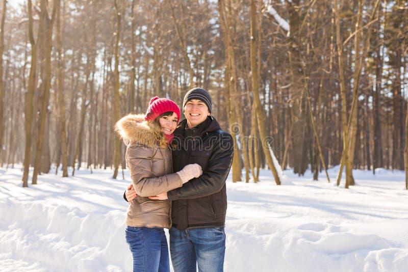 Les jeunes couples heureux en hiver stationnent avoir l'amusement Famille à l'extérieur Amour photographie stock