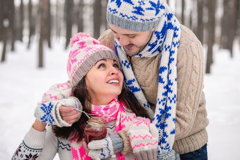 Les jeunes couples heureux en hiver stationnent avoir l'amusement Famille à l'extérieur Baiser d'amour images stock