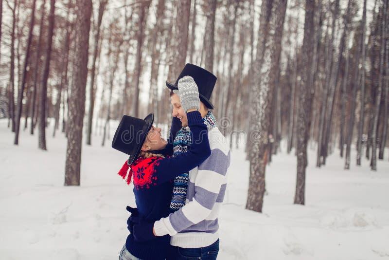 Les jeunes couples heureux en hiver stationnent avoir l'amusement Famille habillée dans des cylindres drôles de chapeaux image libre de droits