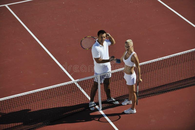 Les jeunes couples heureux jouent le jeu de tennis extérieur photos stock