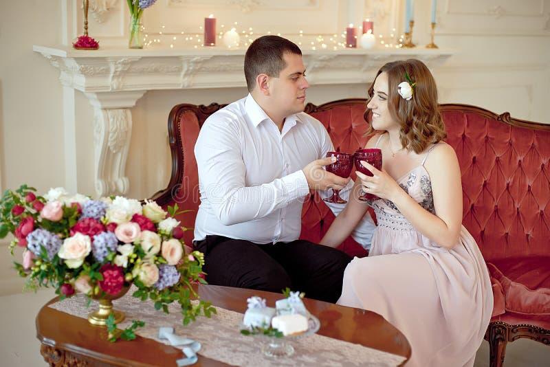 Les jeunes couples heureux ont une date dans la grande pièce blanche avec l'intérieur baroque de style image libre de droits