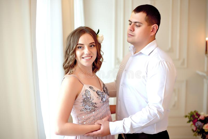 Les jeunes couples heureux ont une date dans la grande pièce blanche avec l'intérieur baroque de style photographie stock libre de droits