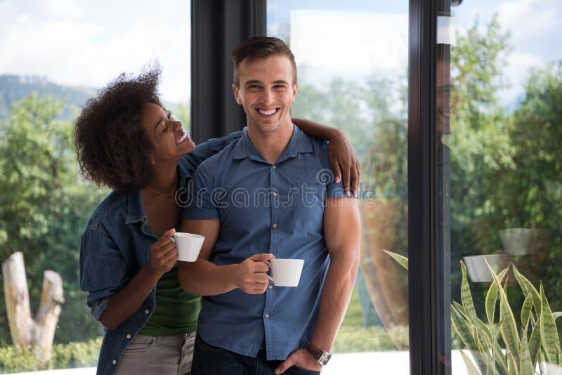 Les jeunes couples heureux romantiques détendent à la maison moderne à l'intérieur photos stock
