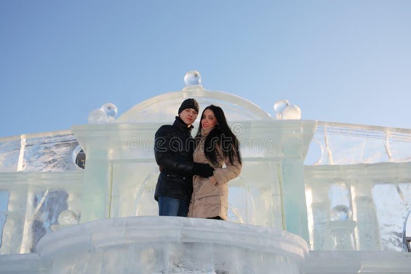 Les jeunes couples heureux s'élèvent sur le balcon glacial près du mur de glace à l'hiver photos libres de droits