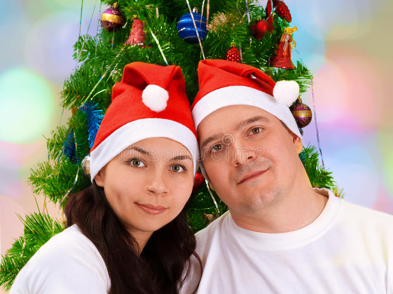 Les jeunes couples heureux s'approchent de l'arbre de Noël photographie stock libre de droits