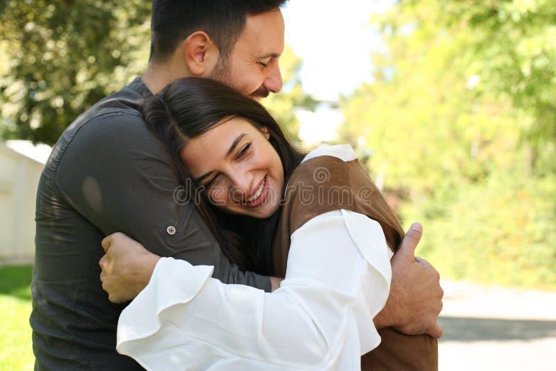Les jeunes couples heureux se reposant dans la ville garent étreindre photo libre de droits