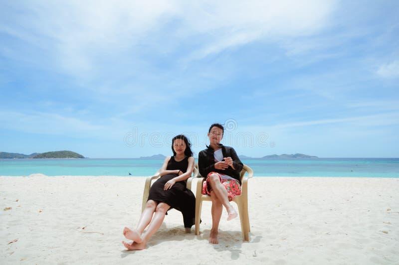 Les jeunes couples heureux se reposent sur la chaise sur la plage images stock